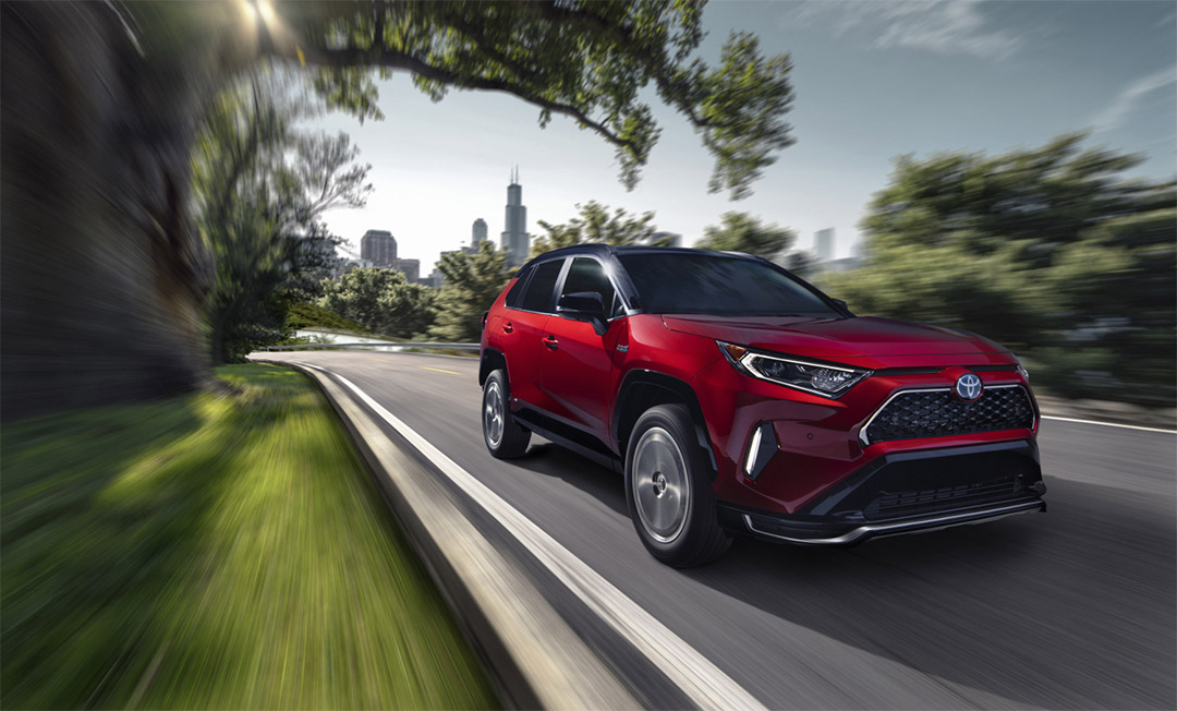 three quarter front view of the 2021 Toyota RAV4 Prime on a road