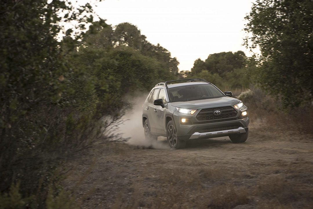 frontal view of the 2021 Toyota RAV4 as it rounds a corner on a dirt road