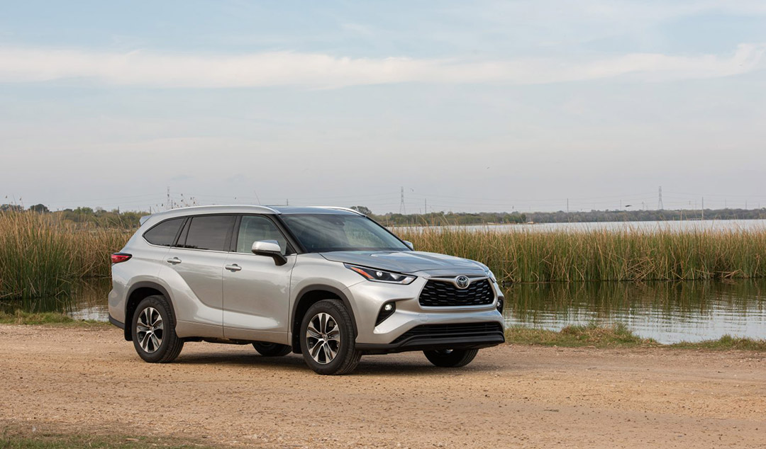 three quarter front view of the 2021 Toyota Highlander stopped close to a body of water
