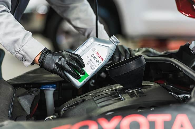 A mechanic pouring TOYOTA OW-20 engine oil into the Toyota car