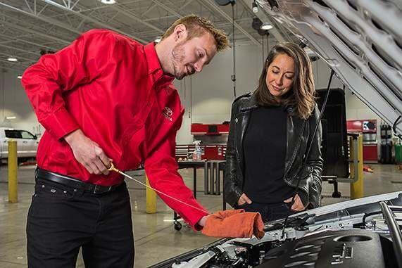 Toyota mechanic checking oil at customer's car