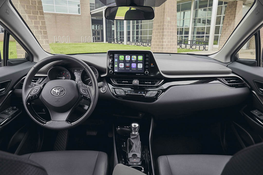 View of the living space inside of the 2021 Toyota C-HR with the steering wheel and main controle panel