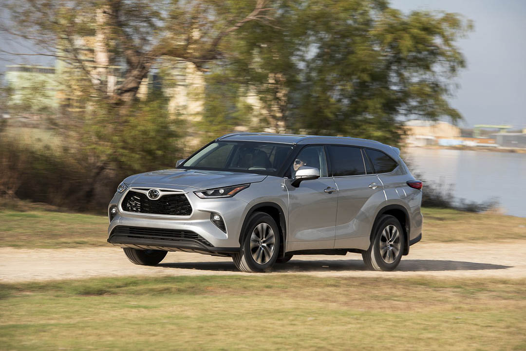 three quarter front view of the 2021 Toyota Highlander on a dirt road