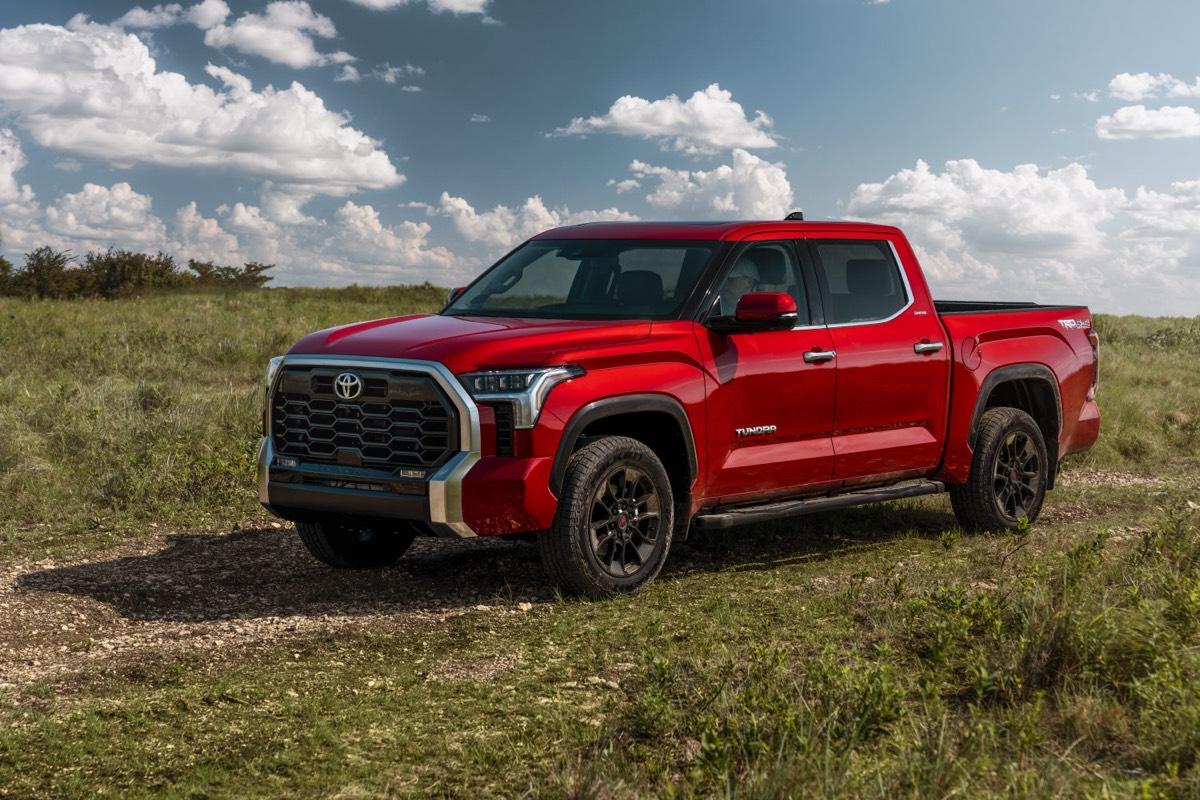 Vue 3/4 avant du Toyota Tundra Limited 2022 couleur rouge garé dans un champs d'herbes