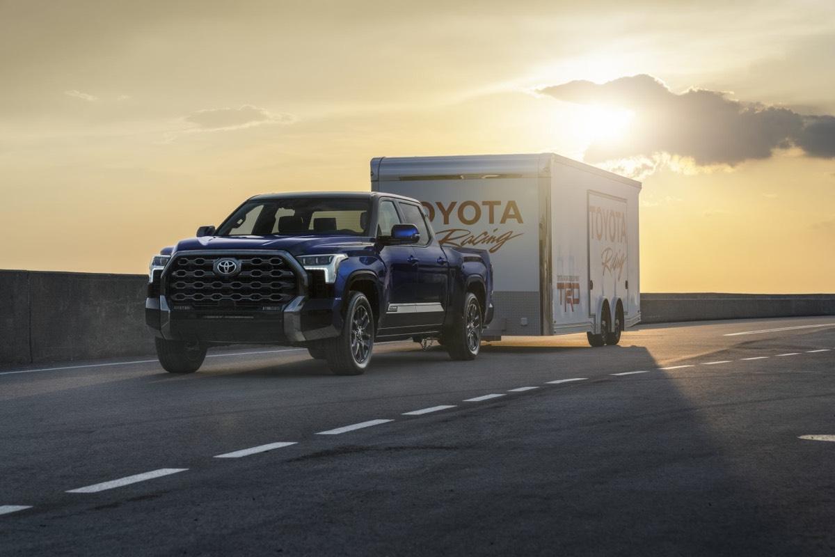 Vue 3/4 avant du Toyota Tundra Platinum 2022 remorquant la caisse TOYOTA Racing sur la route