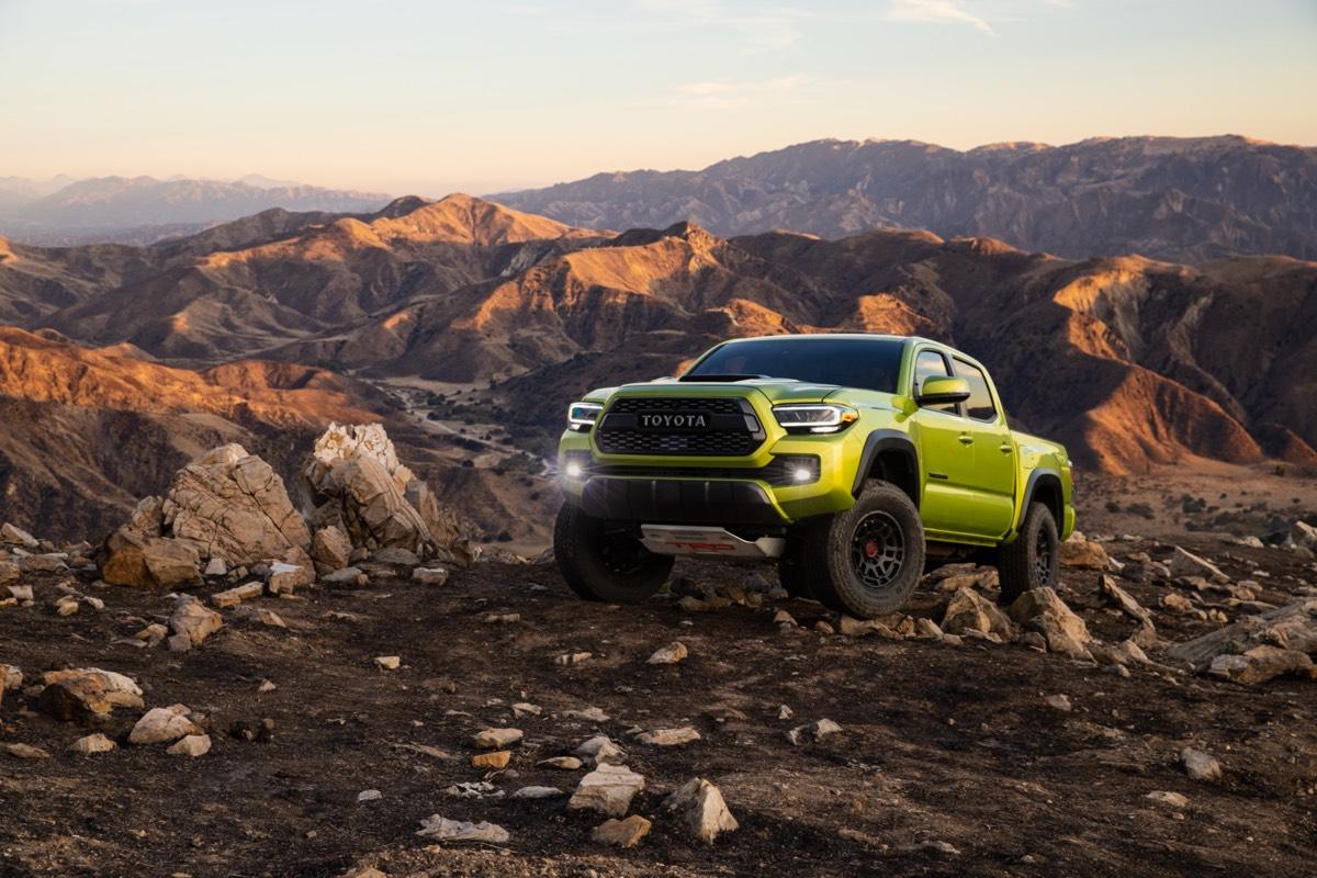 Le Toyota Tacoma TRD Pro 2022 de couleur Lime électrique avec ses phares de route automatiques allumés et garé sur une montagne
