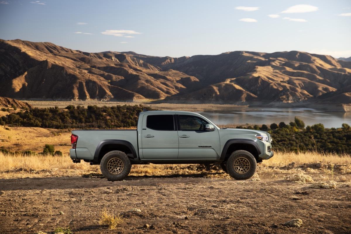 Vue latérale du Toyota Tacoma édition Trail 2022 de couleur Roche Lunaire garé non loin des montagnes